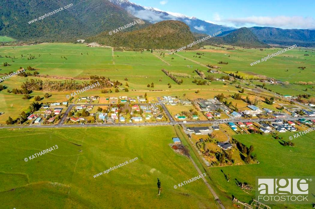 Stock Photo: Aerial view of small New Zealand village, town surrounded by green fields and farms. Whataroa, South Island. New Zealand.