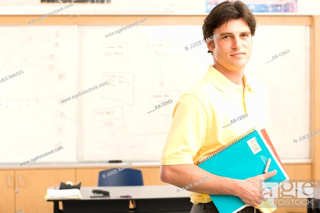 Stock Photo: Teacher with books in classroom, portrait.