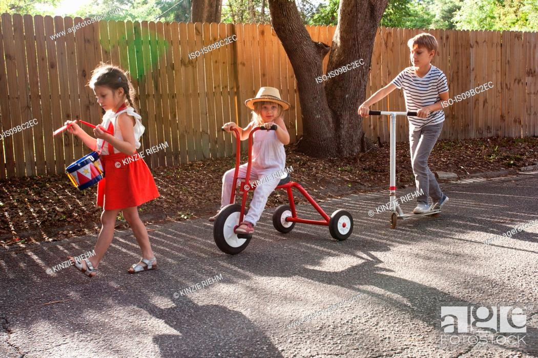 Stock Photo: Three children in mini parade, banging drum, riding tricycle and using scooter.