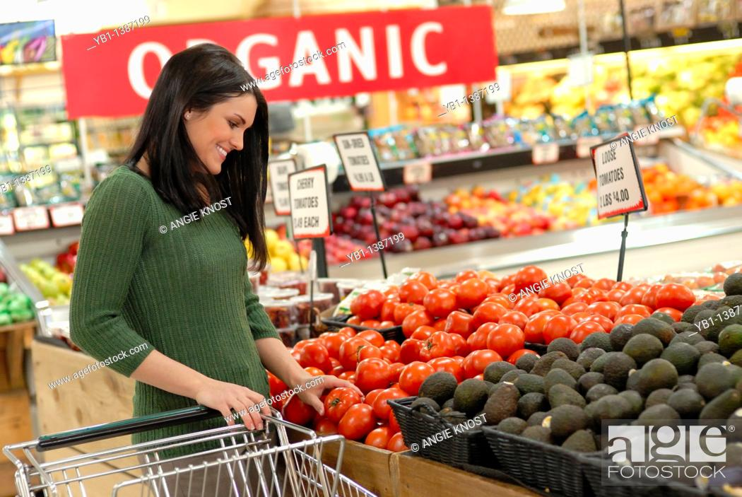 Stock Photo: Attractive woman grocery shopping, in the produce section  An 'Organic' sign in the background shows she is shopping for organic produce.