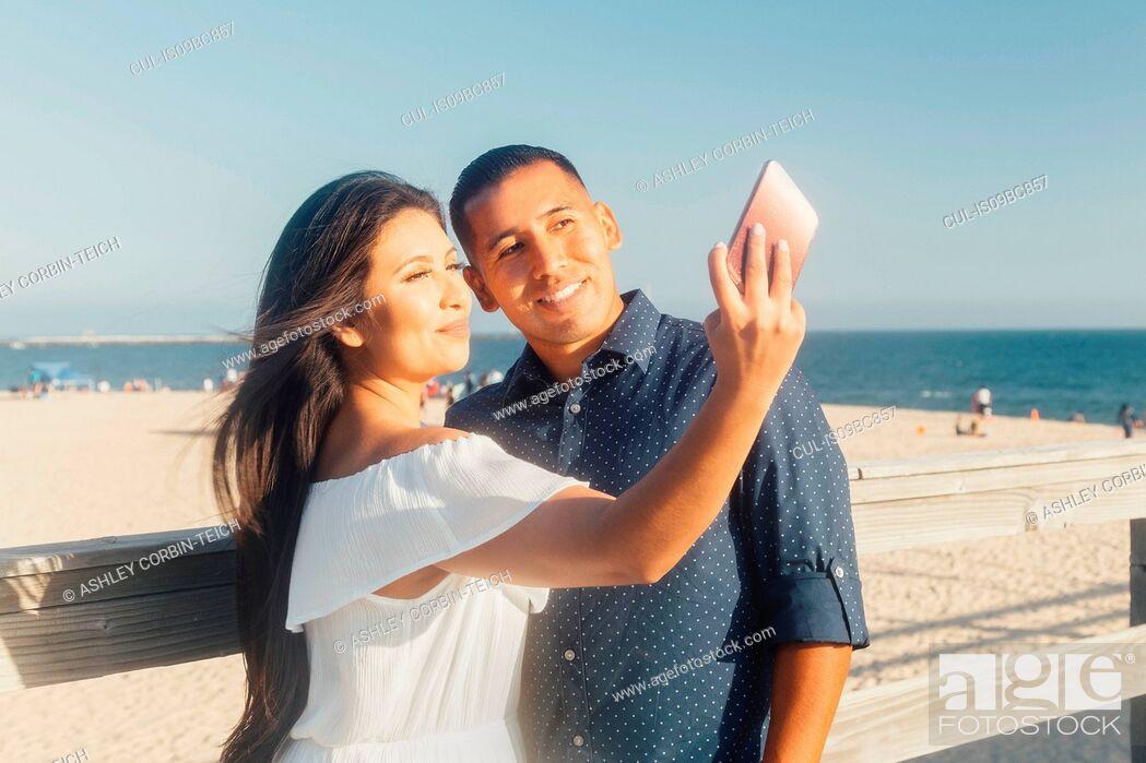 Stock Photo: Couple beside beach, talking selfie, using smartphone, Seal Beach, California, USA.
