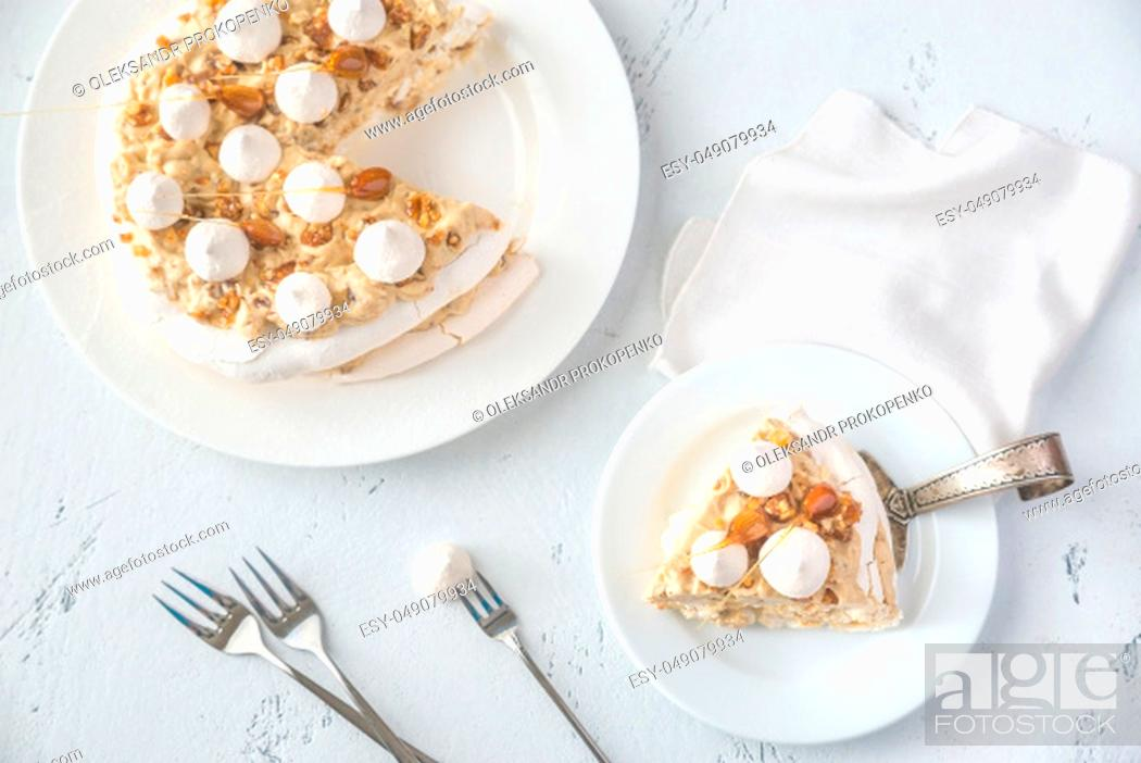 Stock Photo: Pavlova cake with caramel and almonds on the wooden background.