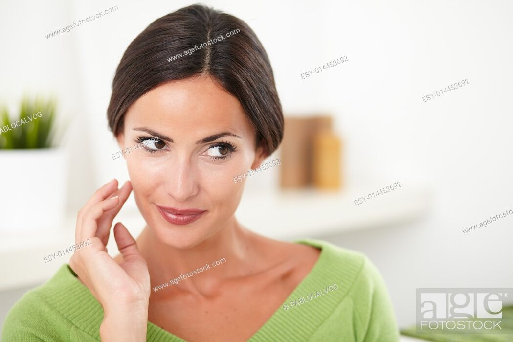 Stock Photo: Young confident caucasian woman with hand on face looking away at indoors - copy space.