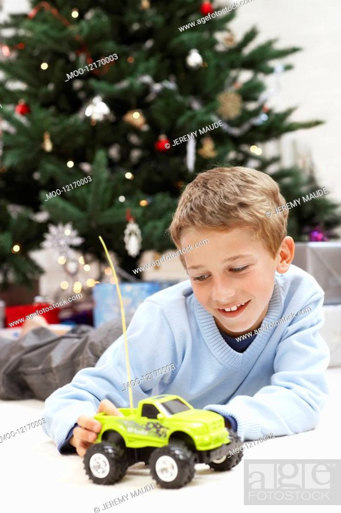 Stock Photo: Little Boy Playing with Toy Truck by christmas tree.