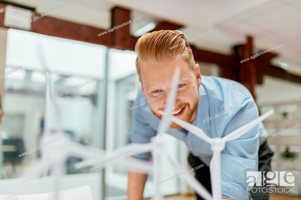 Stock Photo: Businessman in office looking at models of wind turbines.