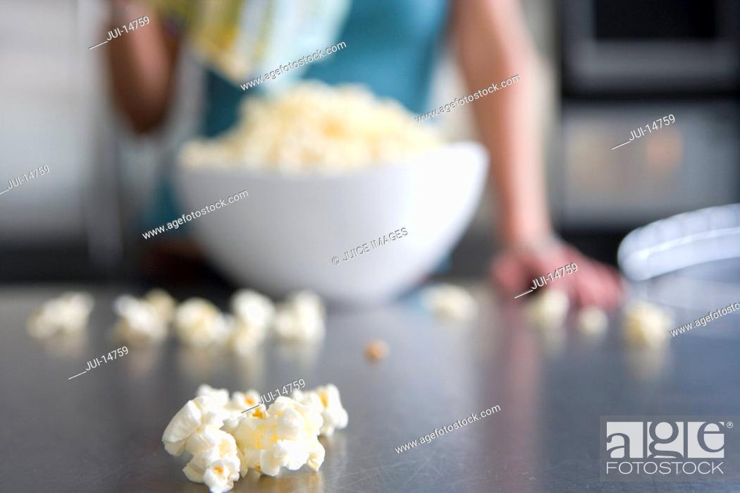 Stock Photo: Woman with popcorn in kitchen.