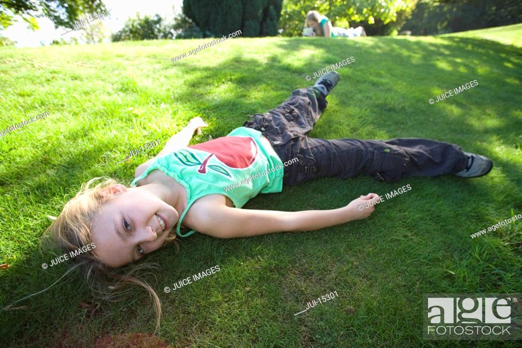 Stock Photo: Girl 8-10 laying on grass, portrait.