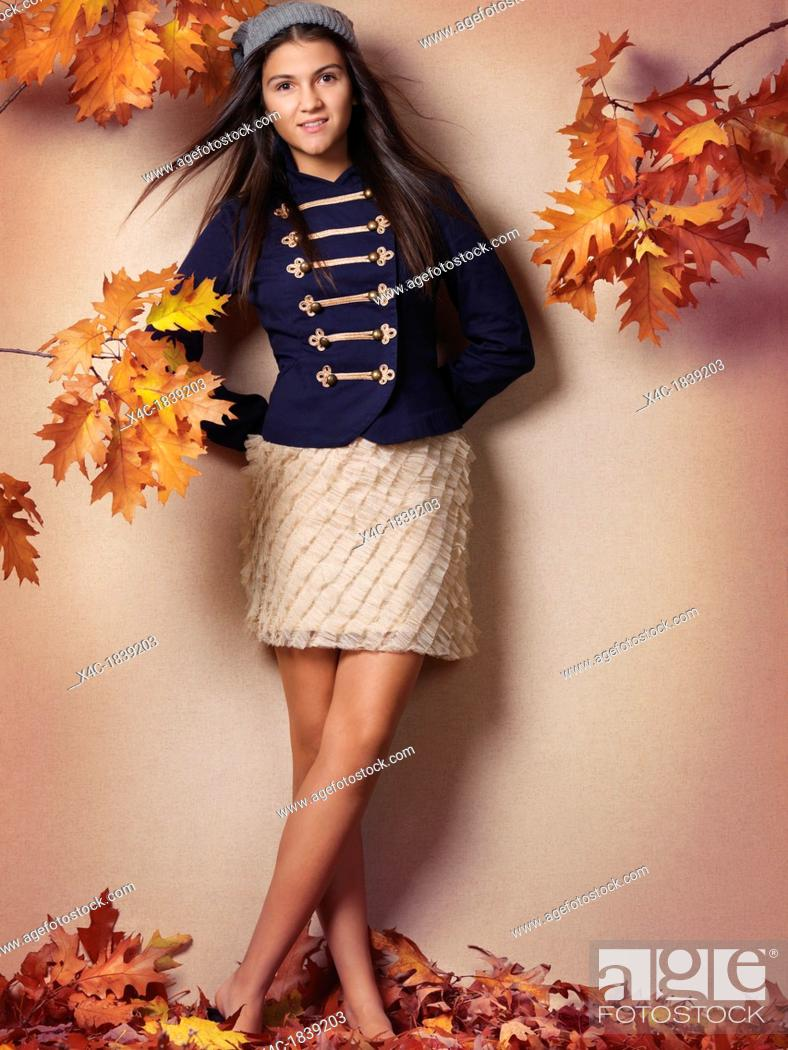 Stock Photo: Smiling teenage girl artistic fall fashion photo with red autumn leaves.