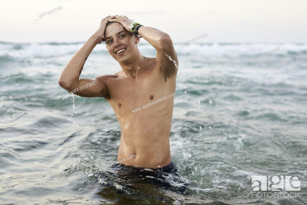 Photo de stock: Young man in sea water, Potamos beach, in holiday destination Malia, Crete, Greece.