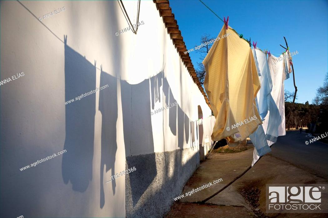 Stock Photo: Clothes drying in the sun, shadow on the wall. Andalusia, Spain.