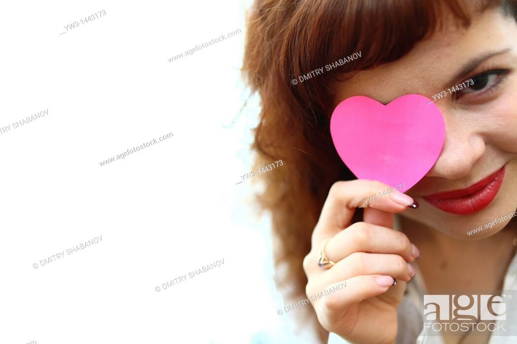 Stock Photo: Pretty redhead young woman portrait with heart indoors.