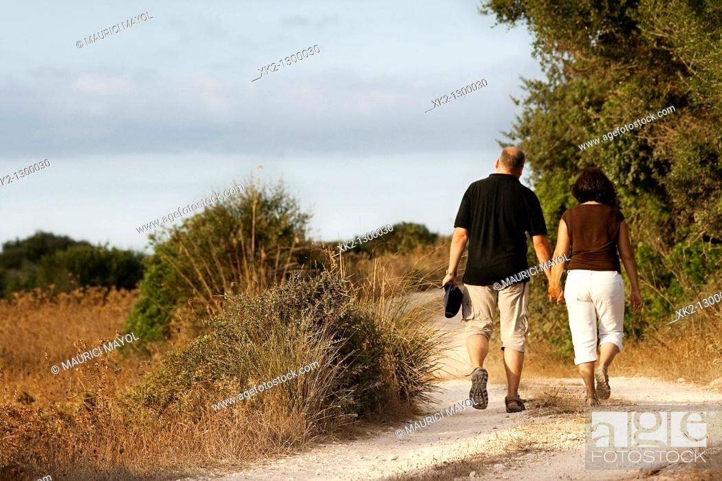 Stock Photo: Couple walking in the countryside. Minorca, Balearic Islands, Spain.