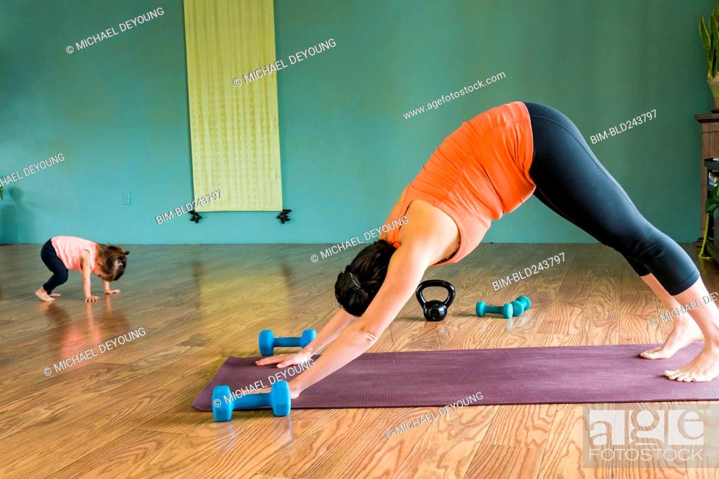 Stock Photo: Mixed Race expectant mother and daughter practicing yoga.