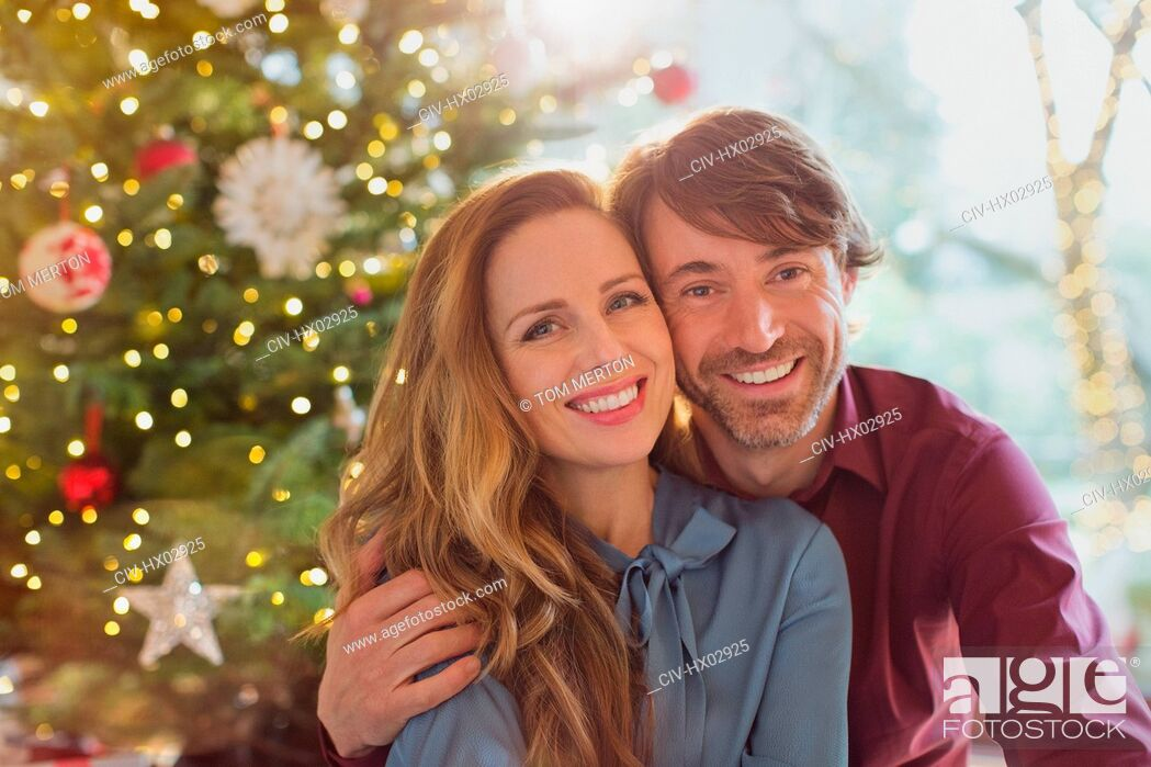 Imagen: Portrait smiling couple hugging in front of Christmas tree.
