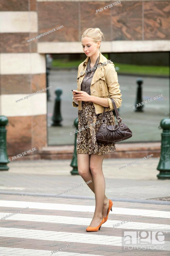 Stock Photo: Businesswoman crossing the road while using a mobile phone.