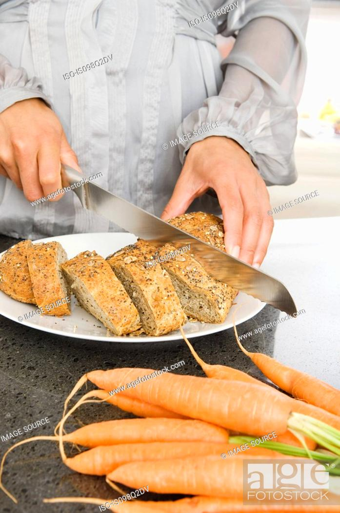Stock Photo: A woman slicing bread.