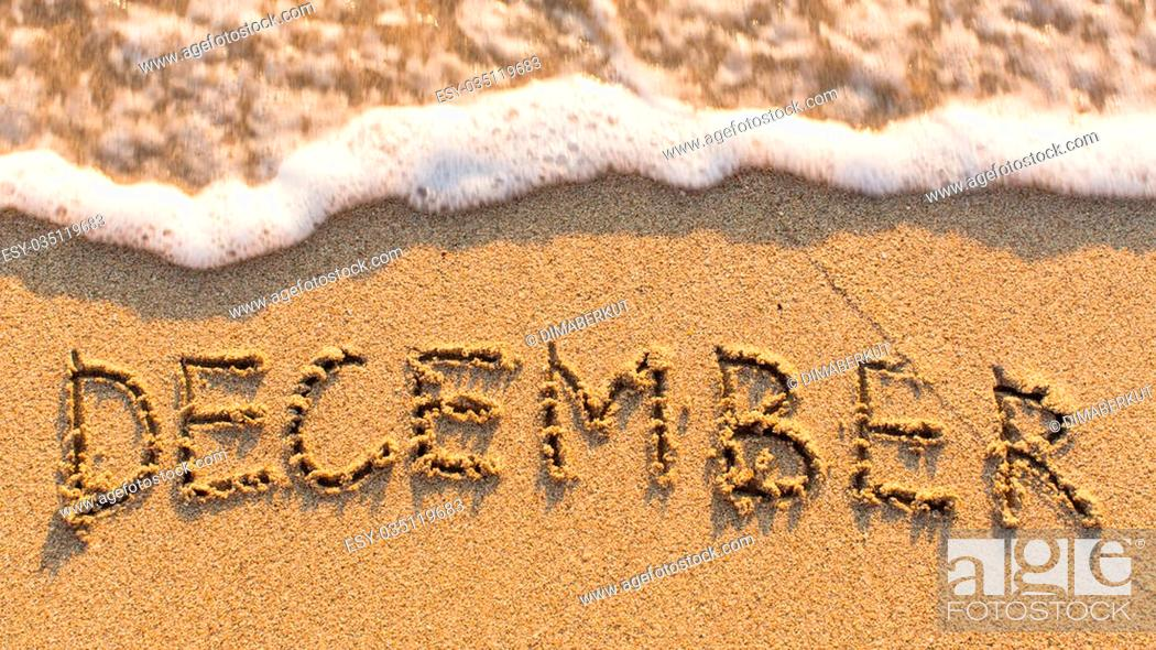 Stock Photo: Inscription DECEMBER on a gentle beach sand with the soft wave (months of the year series).