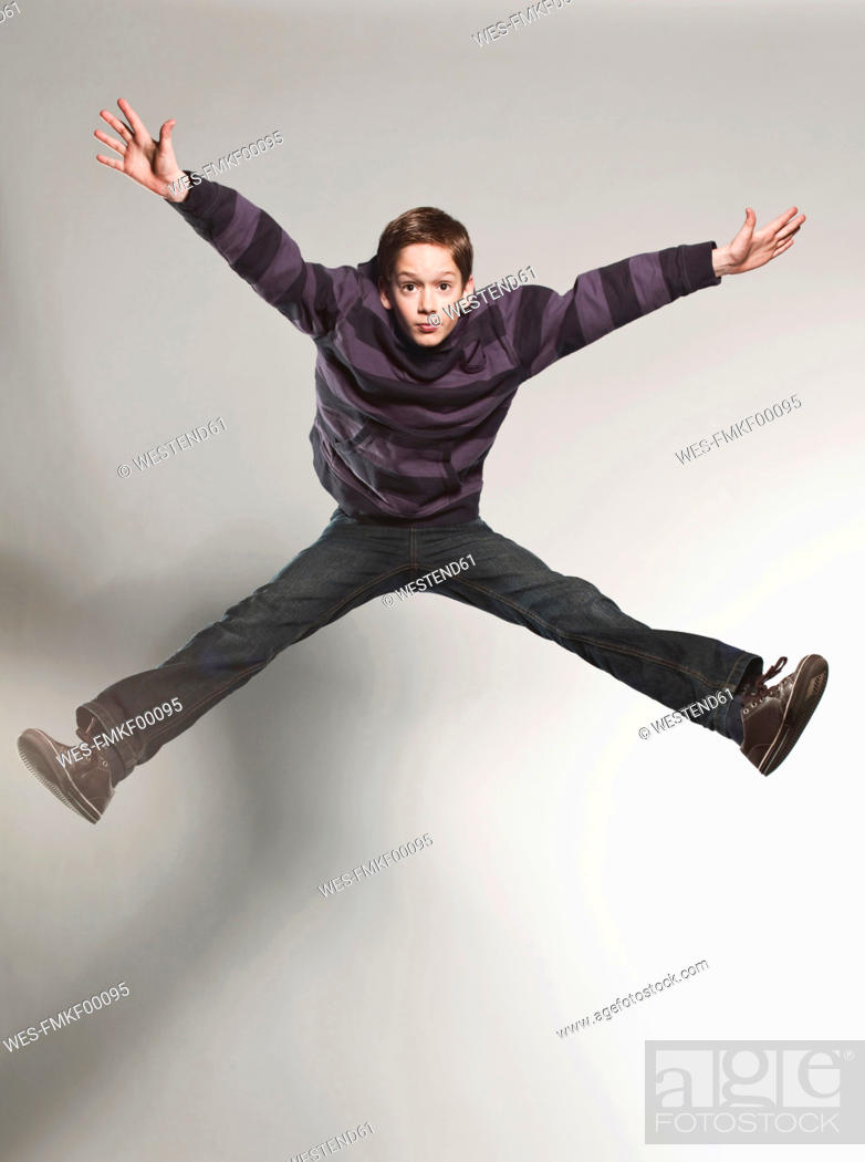 Stock Photo: Boy 12-13 jumping against gray background.