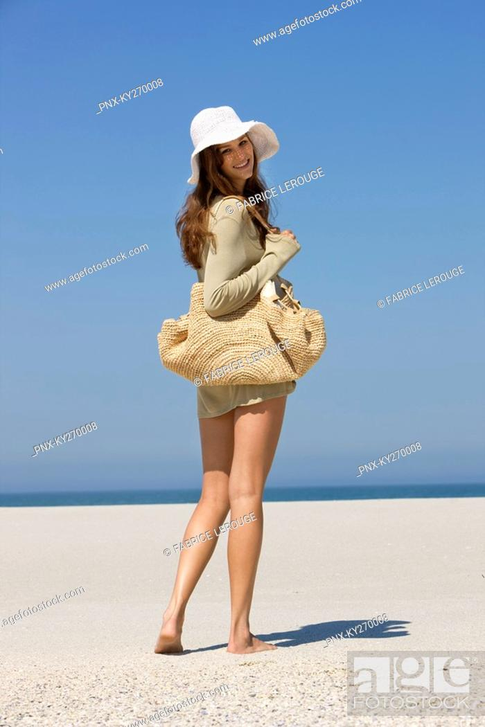 Stock Photo: Woman walking on the beach and smiling.