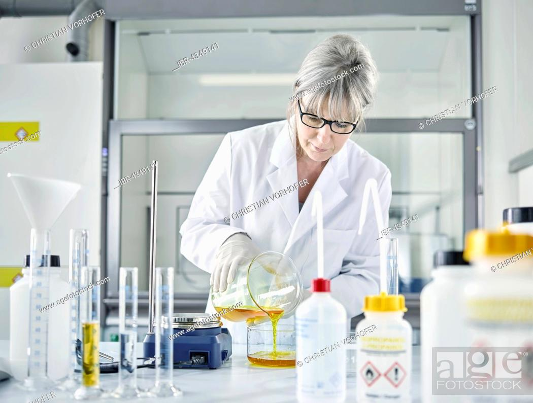 Stock Photo: Female analytical chemist, gray hair, 50-55 years, filling a chemical mixture of water and Potassium ferrocyanide into a glass container, Wattens.
