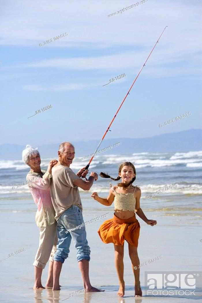 Stock Photo: Girl 7-9 by grandparents fishing on beach, smiling, portrait.