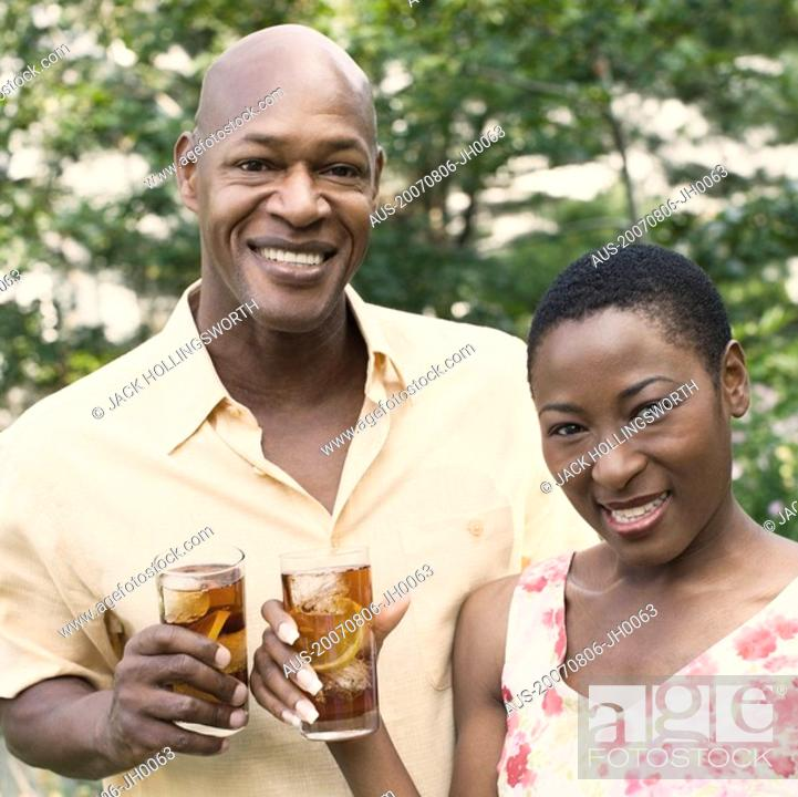 Stock Photo: Portrait of a couple holding glasses of ice tea and smiling.