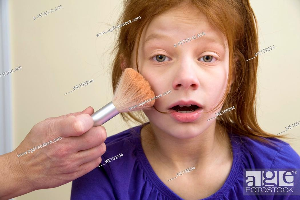 Stock Photo: Makeup being applied to a preteen redhead girl.