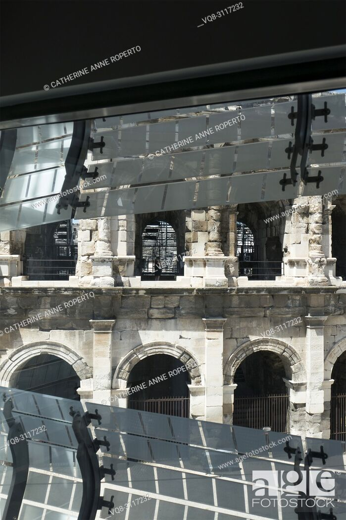 Imagen: Vertical view of the Arena at Nimes through the reflective cladding of the Roman Museum, with their geometric forms mirroring the metal seating of the.