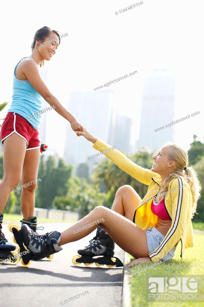 Stock Photo: Woman on rollerblades helping friend up from ground.