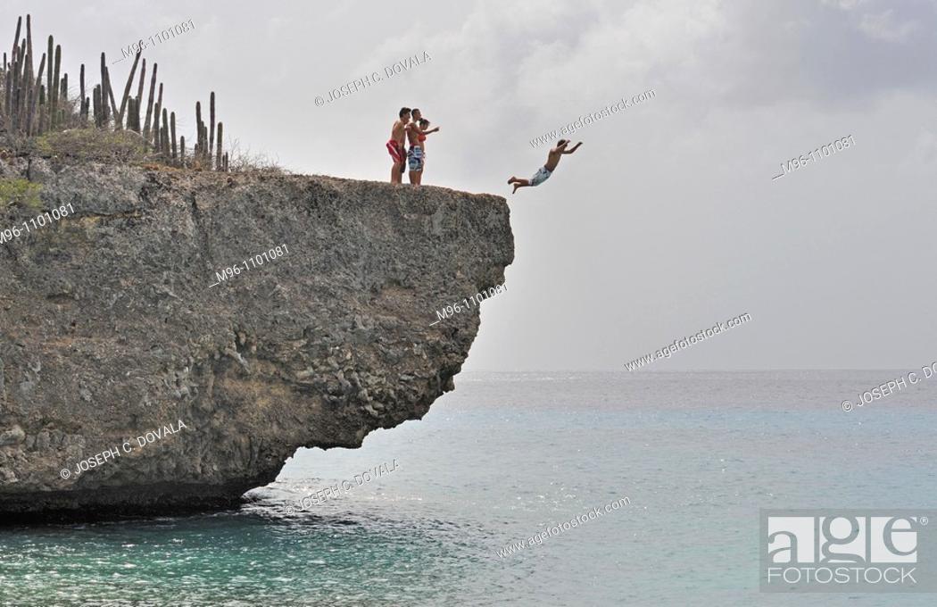 Stock Photo: Kids jumping off cliff into ocean, Bonaire Island, Netherlands Antilles, Caribbean.