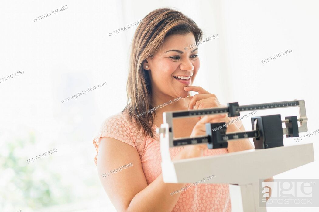 Stock Photo: Happy woman standing on scale.