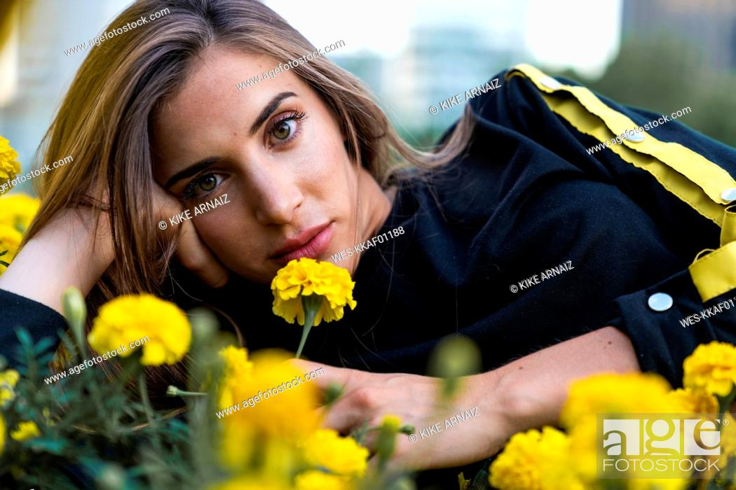 Stock Photo: Portrait of attractive young woman lying in flower meadow.