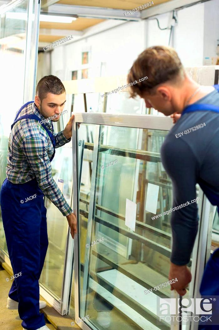 Stock Photo: Two careful workmen checking windows at factory.