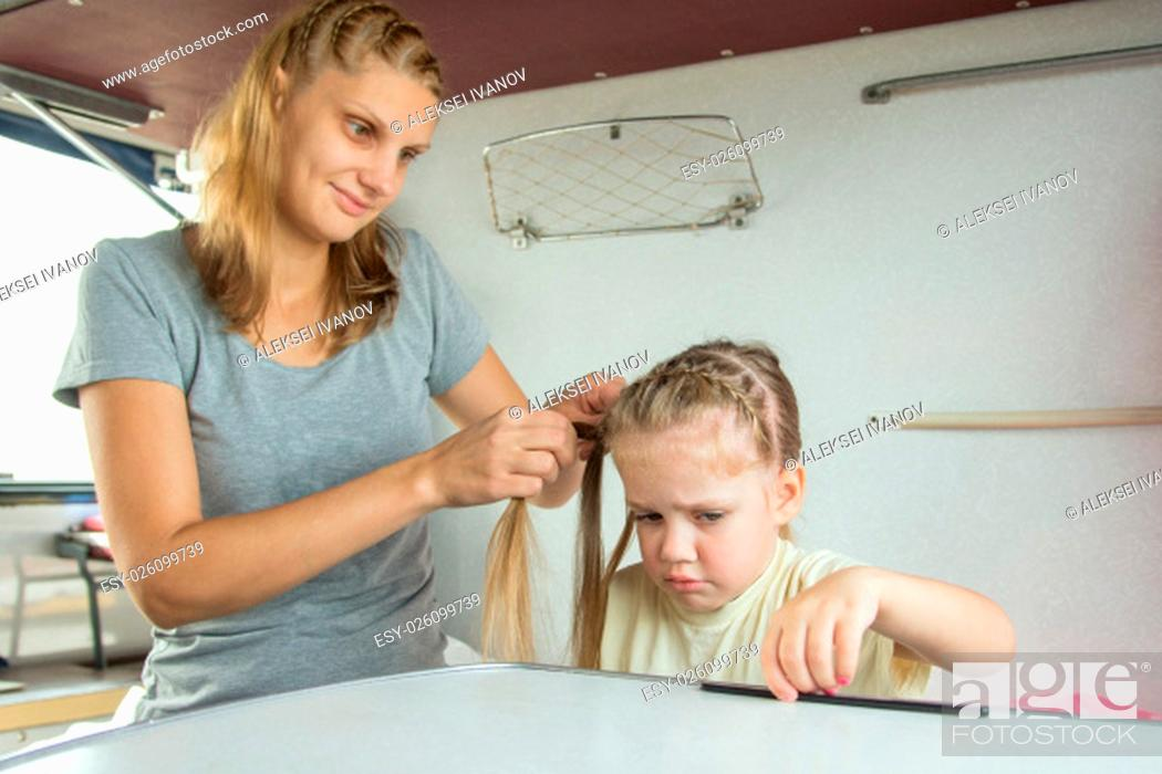 Stock Photo: Young mother combing her long hair a four-year daughter on a cot in a train.
