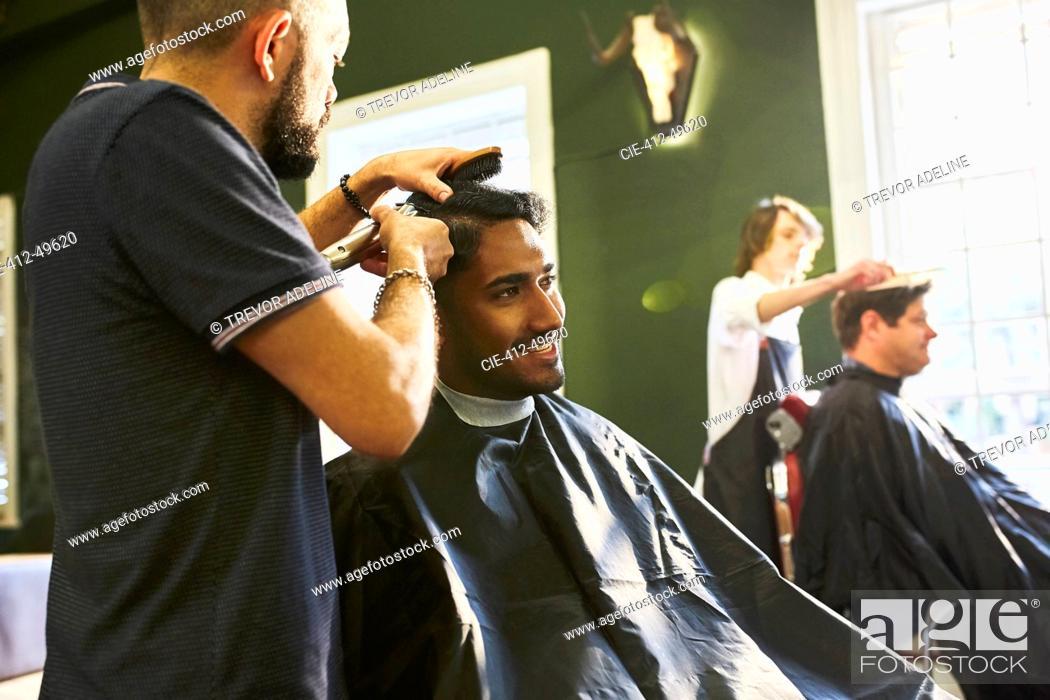 Imagen: Smiling man receiving haircut at barbershop.