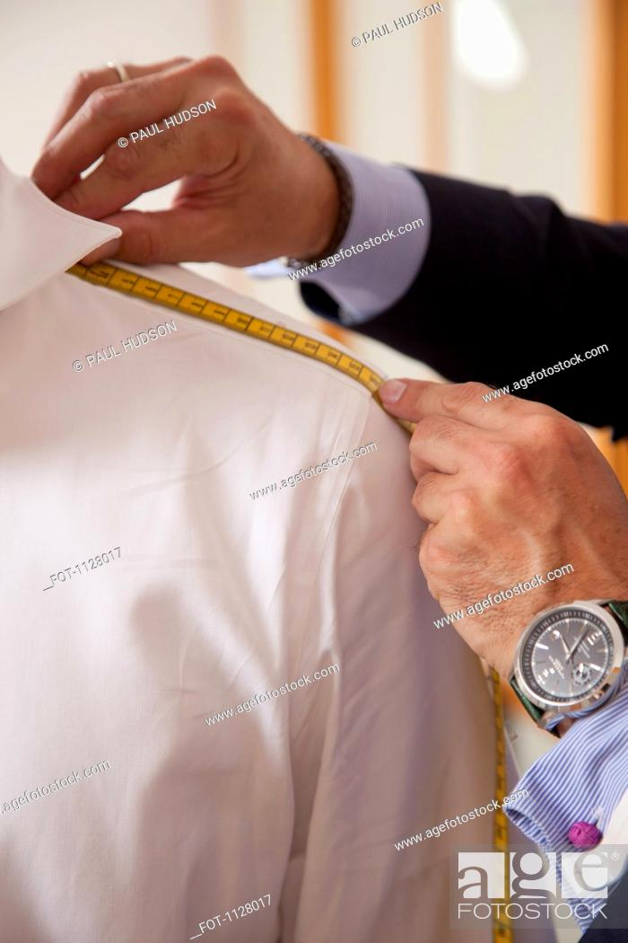 Stock Photo: Detail of a tailor measuring the shoulder of a man.