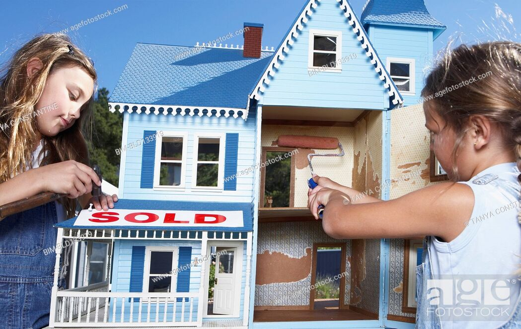 Stock Photo: Mixed race girls fixing up doll house for sale.