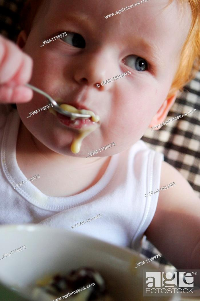 Stock Photo: A baby feeding himself in a high chair, using a spoon.