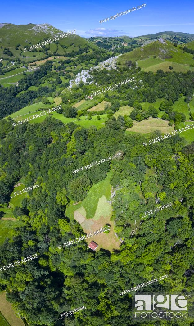 Imagen: Spring landscape of mountains, meadows of mowing and cabins pasiegas in the Miera Valley, Cantabria, Spain, Europe.
