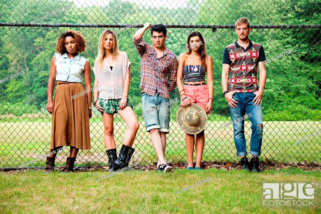 Stock Photo: Portrait of friends standing against chain link fence.