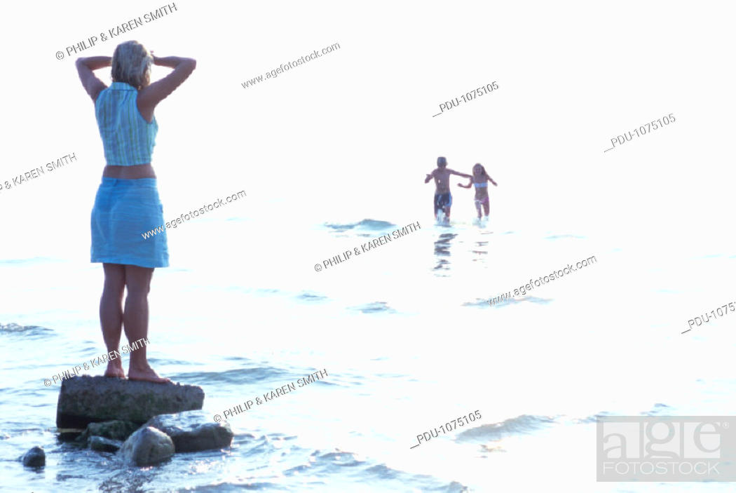 Stock Photo: Italy, Lake Garda, mature woman on rock watching children play in surf.