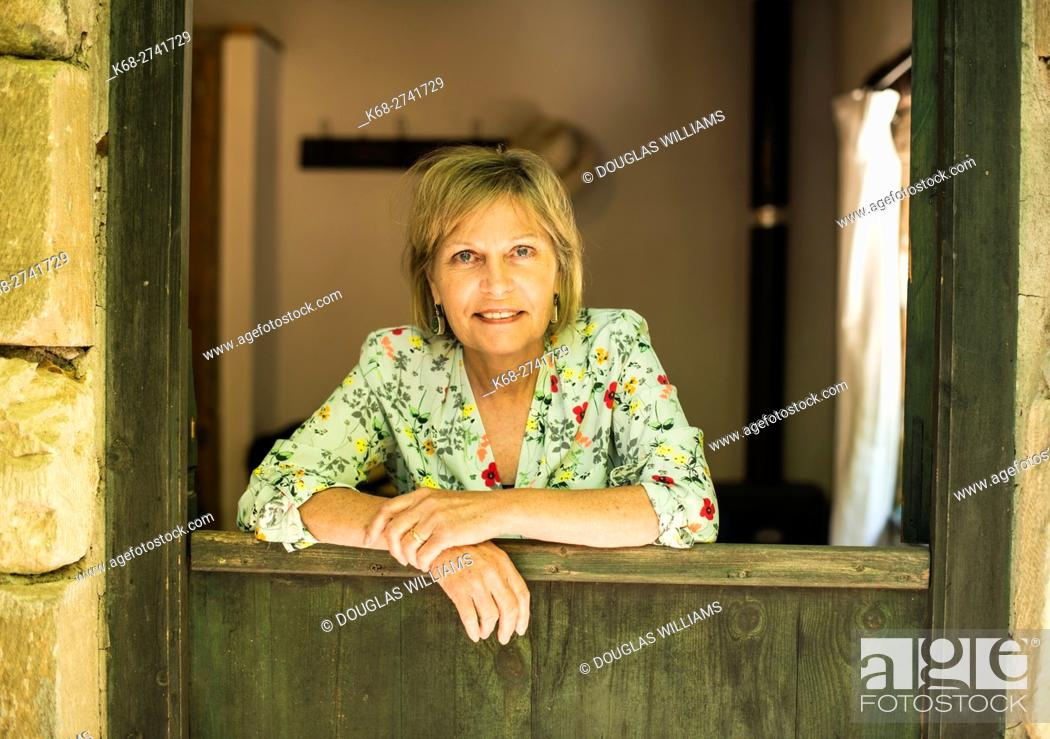 Stock Photo: A woman, 65, smiling at a doorway in Milia Mountain Retreat, Chania, Crete, Greece.