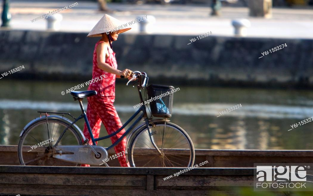Stock Photo: Conical hat woman pushes bicycle over footbridge Hoi An Vietnam.