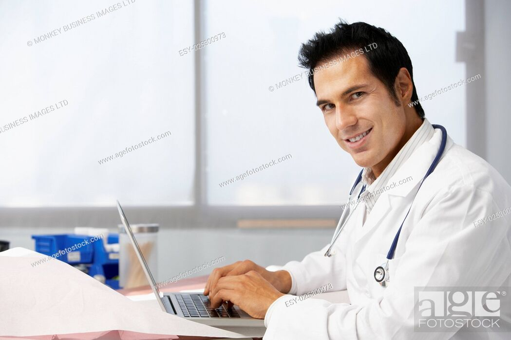 Stock Photo: Male Doctor In Surgery Using Laptop.