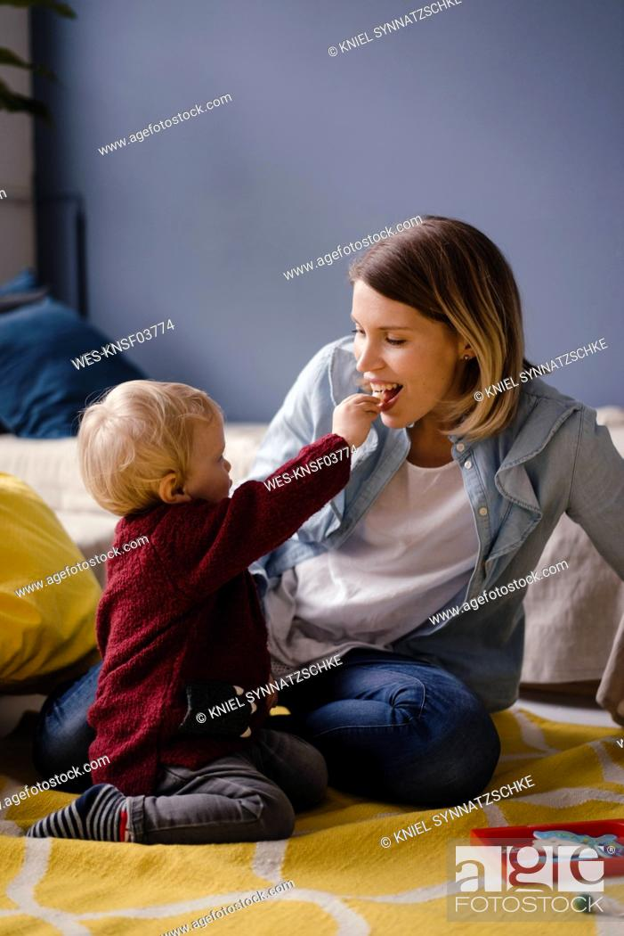 Stock Photo: Mother playing with her baby son, who is feeding her.