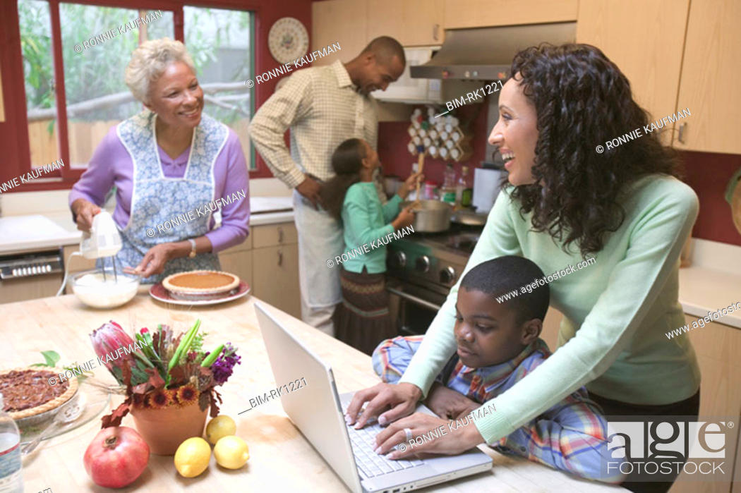 Stock Photo: Woman using a laptop in busy kitchen.