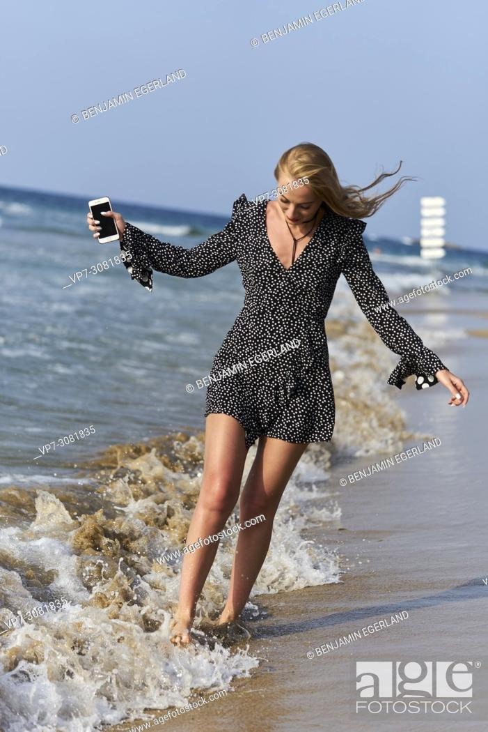 Photo de stock: Greece, Crete, Malia, woman with smart phone walking on beach between waves.