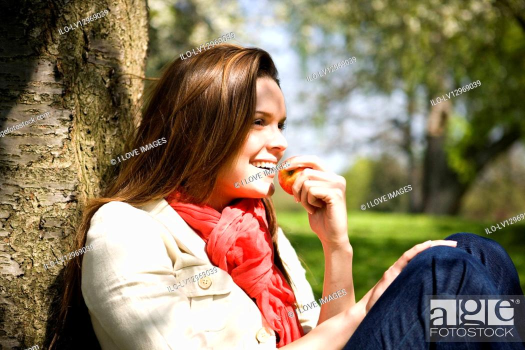 Stock Photo: A young woman eating an apple, outdoors.