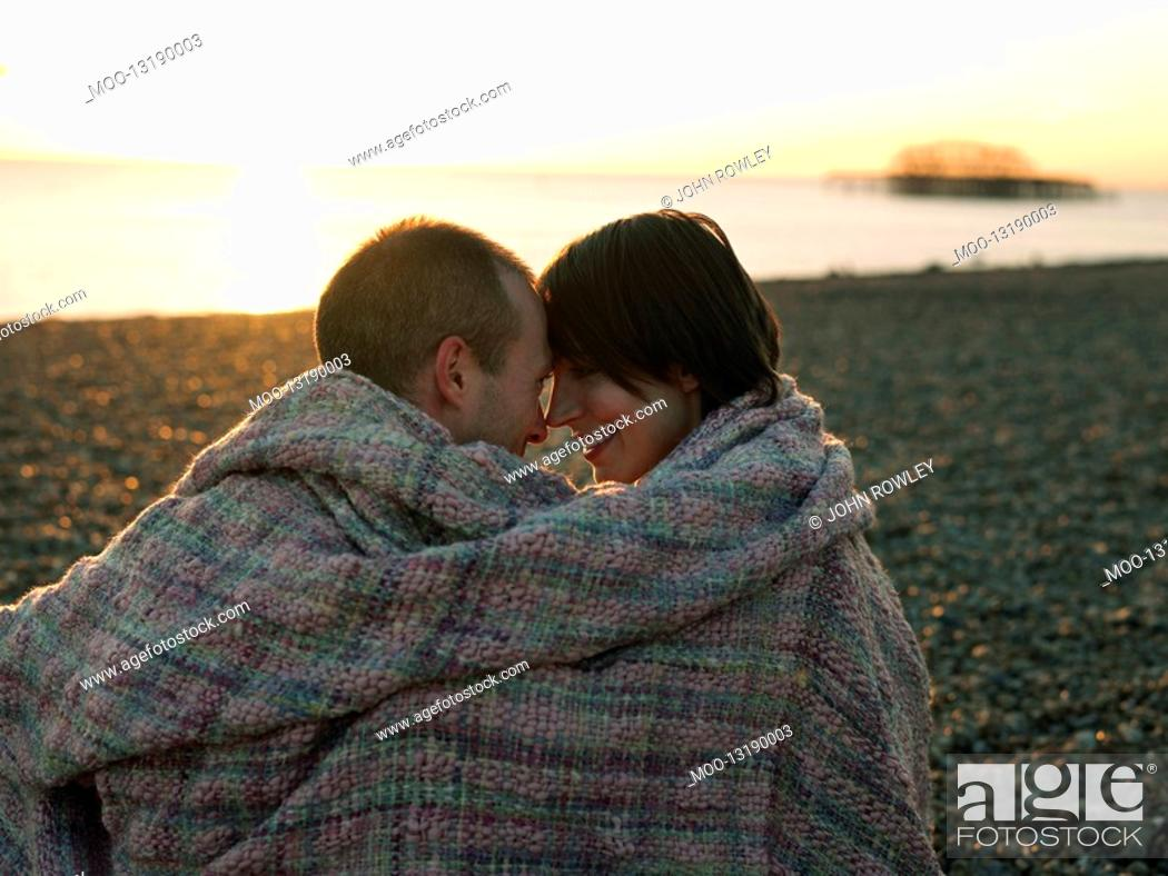 Stock Photo: Couple wrapped in blanket sitting on beach at sunset.
