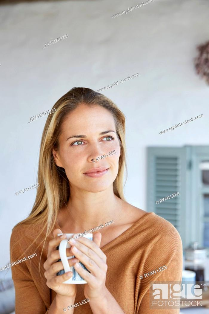 Stock Photo: Serene woman drinking coffee and looking away on patio.